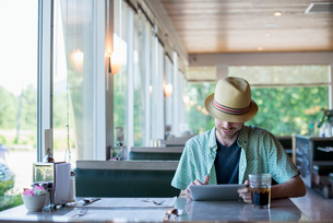 A man wearing a hat sitting in a diner using a digital tablet.の写真素材 [FYI02247908]