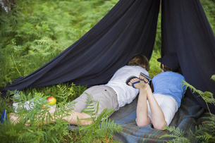 Two boys camping in the New Forest lying under a canvas shelter.の写真素材 [FYI02247923]