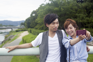 A couple, a man and woman in a Kyoto park.の写真素材 [FYI02247924]