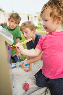 Three children in a garden, painting a dog house.の写真素材 [FYI02248002]