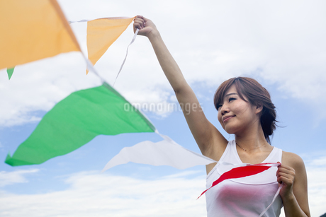 A woman in a Kyoto park holding up a colourful row of flags.の写真素材 [FYI02248044]