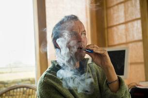 A man using an electronic cigarette, vaping.の写真素材 [FYI02248099]