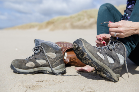 Young woman taking her hiking boots off on the beach at Harlech.の写真素材 [FYI02248102]