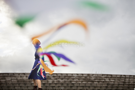 An artist during a performance moving a line of flags or streamers.の写真素材 [FYI02248106]