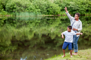 Two brothers playing by a lake.の写真素材 [FYI02248107]