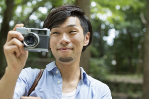 A man in a Kyoto park holding a camera, taking a picture.の写真素材 [FYI02248130]