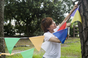 A woman in a Kyoto park holding up a colourful row of flags.の写真素材 [FYI02248153]