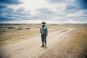 Man wearing cowboy hat and cowboy boots standing on a country lane in the Canadian Prairie.の写真素材 [FYI02248155]