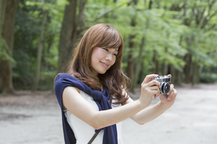 A woman in a Kyoto park holding a camera, preparing to take pictures.の写真素材 [FYI02248156]