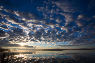A dramatic cloud pattern across the sky and the sun setting over the waters of a lake.の写真素材 [FYI02248162]