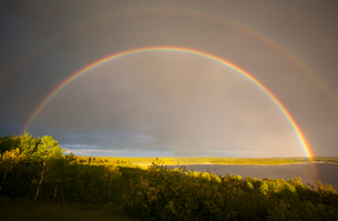 A double rainbow in the sky arching over the land.の写真素材 [FYI02248191]