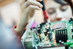 A woman using an electronic screwdriver on a computer circuitboard.の写真素材 [FYI02248220]