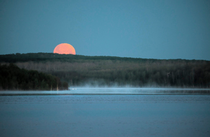 A red moon setting over a lake. Moonlight.の写真素材 [FYI02248223]