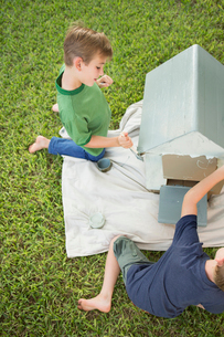 Two brothers in a garden, painting a dog house.の写真素材 [FYI02248226]