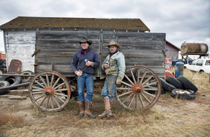 Two men in cowboy hats and cowboy boots leaning against a wooden wagon.の写真素材 [FYI02248247]