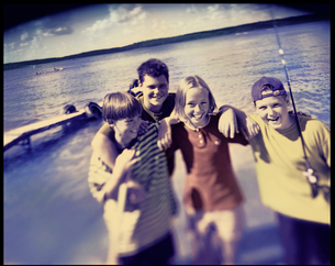 Four children, pre teenagers laughing on the lake shore. Summer vacation.の写真素材 [FYI02248281]