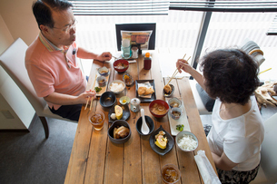Woman and man sitting at a table, eating Japanese Food with chopsticks.の写真素材 [FYI02248289]