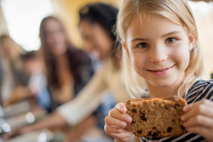 A young girl with a large cookie.の写真素材 [FYI02248327]