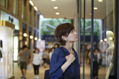 A woman in a shopping mall looking at a shop window display.の写真素材 [FYI02248346]