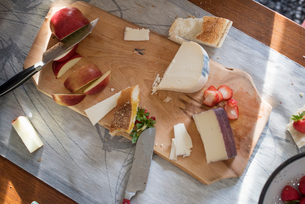 Knives and a wooden chopping board with a selection of cheeses, apples and bread.の写真素材 [FYI02248349]