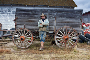 Man in cowboy hat and cowboy boots leaning against a wooden wagon.の写真素材 [FYI02248350]