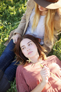 An apple orchard in Utah. Two women lying in the grass.の写真素材 [FYI02248392]