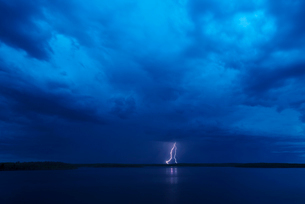A lightning strike reflected in the water of a lake. Dark stormy dramatic sky.の写真素材 [FYI02248419]