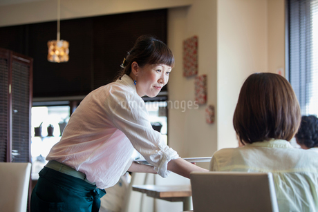 Waitress serving a woman seated at a table in a cafe.の写真素材 [FYI02248433]