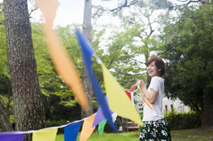 A woman in a Kyoto park holding up a colourful row of flags.の写真素材 [FYI02248435]