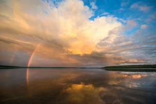 A rainbow and a dramatic cloud formation over a lake.の写真素材 [FYI02248439]