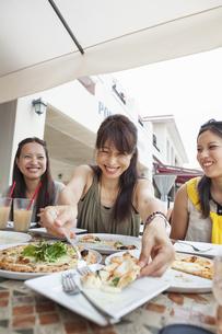 Three women enjoying a meal.の写真素材 [FYI02248440]