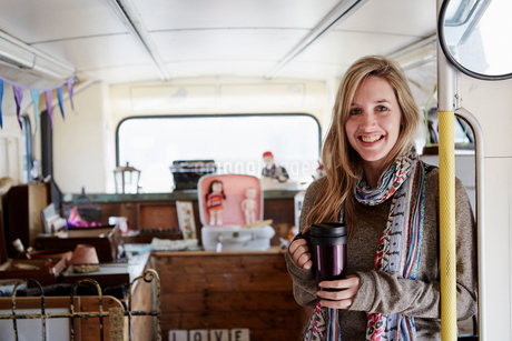 A woman standing in a bus converted into a vintage shop at a flea market surrounded by vintage objecの写真素材 [FYI02248447]