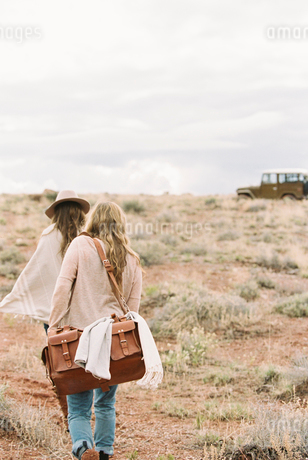 Two women walking towards a 4x4 parked in a desert.の写真素材 [FYI02248449]