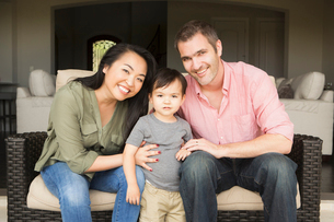 Smiling man and woman sitting side by side on a sofa, posing for a picture with their young son.の写真素材 [FYI02248472]