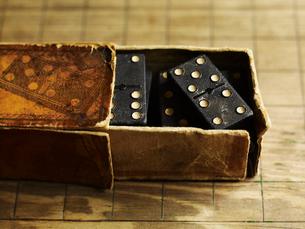 Domino game tiles in a well worn cardboard box.の写真素材 [FYI02248481]