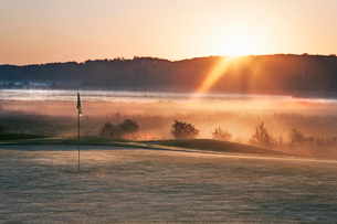 Glowing dawn light on a golf course green. The sun just appearing above a mountain range.の写真素材 [FYI02248482]