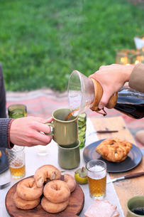 An apple orchard in Utah. Two people sitting at a table with food and drink, pouring coffee.の写真素材 [FYI02248486]