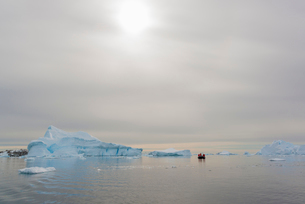 View of a group of people in a rubber boat near and iceberg in the Antarctic.の写真素材 [FYI02248491]