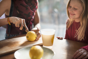 A woman and a smiling girl sitting at a table, woman slicing a lemon in half.の写真素材 [FYI02248494]