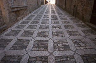 A textured cobblestone alley in the mountain village of Erice in Sicily.の写真素材 [FYI02248508]