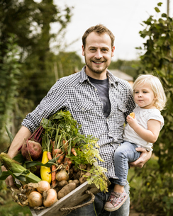 Man standing in his allotment with his daughter, smiling, holding a box full of freshly picked vegetの写真素材 [FYI02248514]