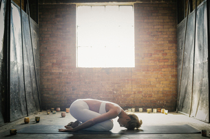 A blonde woman kneeling on a mat on the floor, stretching in a yoga pose, surrounded by lit candles.の写真素材 [FYI02248516]