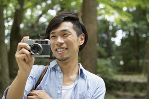 A man in a Kyoto park holding a camera, taking a picture.の写真素材 [FYI02248520]