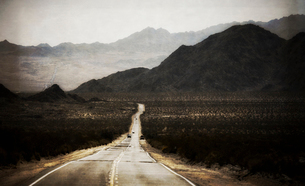 A road leading into the distance, to a range of mountains. Desert scenery, cars on the road.の写真素材 [FYI02248541]