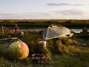 An upturned fishing boat by a narrow water channel in a flat landscape. Fishing floats and buoys.の写真素材 [FYI02248545]