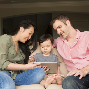 Smiling man and woman sitting side by side on a sofa with their young son, looking at a digital tablの写真素材 [FYI02248549]