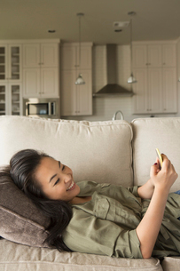 Woman lying on a sofa, smiling, looking at a cell phone.の写真素材 [FYI02248579]