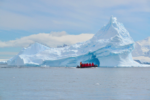 View of a group of people in a rubber boat near a towering iceberg in the Antarctic.の写真素材 [FYI02248584]