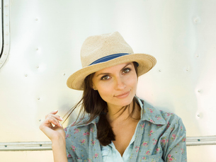 A young woman in a straw hat, her head tilted looking curious.の写真素材 [FYI02248587]