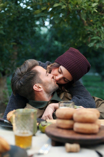 An apple orchard in Utah. A couple kissing, food and drink on a table.の写真素材 [FYI02248593]